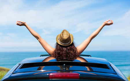Photo pour Rear view of relaxed woman on summer travel vacation to the coast  leaning out car sunroof towards the sea  - image libre de droit