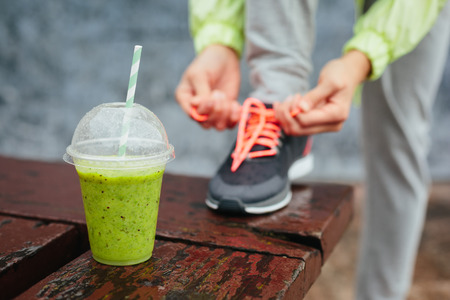 Photo pour Green detox smoothie cup and woman lacing running shoes before workout on rainy day  Fitness and healthy lifestyle concept  - image libre de droit