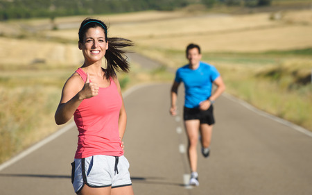 Couple of athletes on running workout in country road   Sporty woman and man exercising together on summer  Healthy and sport lifestyle concept