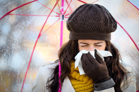 Foto de Woman with cold or flu coughing and blowing her nose with a tissue under autumn rain. Brunette female sneezing and wearing warm clothes. - Imagen libre de derechos