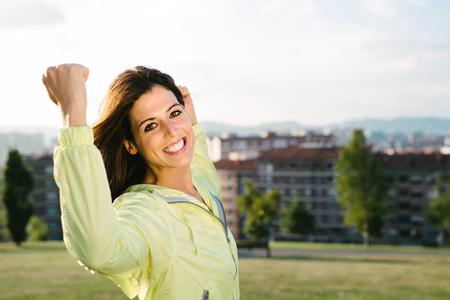 Photo pour Sporty urban woman celebrating sport and fitness lifestyle success. Happy female athlete raising arms after achieving exercising goals in city park. - image libre de droit