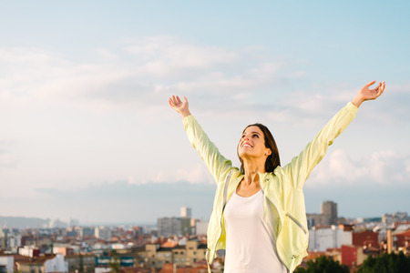 Photo pour Happy woman celebrating fitness and sport exercising success. Successful female athlete raising arms to the sky on city skiline background. - image libre de droit