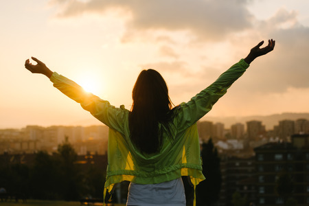 Foto de Back view of a blissful woman celebrating sport and fitness lifestyle success. Female athlete raising arms to the sky after exercising for relax towards beautiful sunset or morning over city skyline. - Imagen libre de derechos