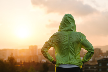 Photo pour Back view of athlete looking sunset over city skyline after exercising. Motivation, sport and fitness lifestyle concept. - image libre de droit