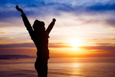 Foto de Blissful woman enjoying freedom and happiness on beautiful sunset towards the ocean and sky. - Imagen libre de derechos