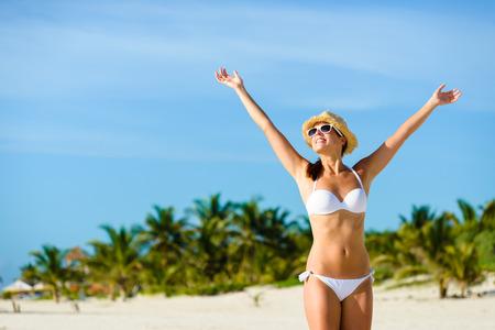 Foto de Beautiful blissful woman in bikini enjoying tropical beach and caribbean summer vacation. Tanned brunette raising arms and enjoying freedom by the sea at Playa Paraiso, Riviera Maya, Mexico. - Imagen libre de derechos