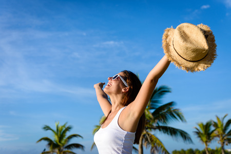 Photo pour Blissful woman on tropical caribbean vacation raising arms to the sky. Freedom and travel concept. Brunette woman enjoying summer holidays. - image libre de droit