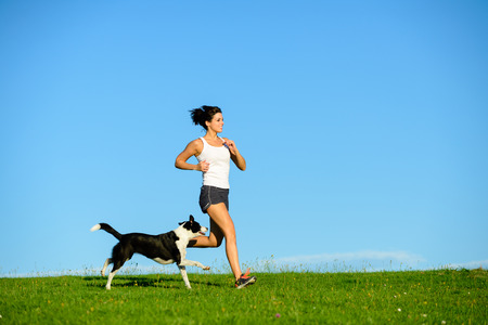 Foto de Woman and dog running and exercising outdoor at grass field on summer or spring. Happy female athlete training with her pet. - Imagen libre de derechos