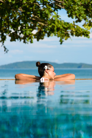 Foto de Relax and spa concept. Woman with a flower in hair relaxing in a pool at Krabi, Thailand. - Imagen libre de derechos