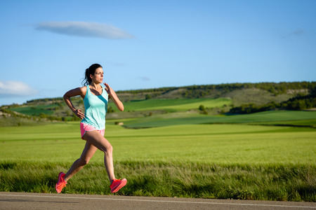 Sporty woman running fast on country side road. Female athlete training outdoor.