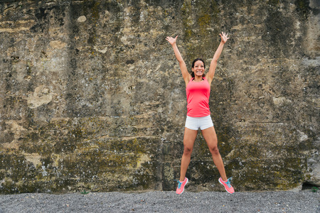 Photo for Happy female athlete jumping for celebrating exercising and fitness success. - Royalty Free Image