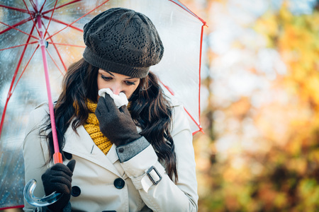 Foto de Sad woman with cold or flu blowing her nose with a tissue under autumn rain. Brunette female sneezing and wearing warm clothes against cold weather. Illness, depression and allergy concept. - Imagen libre de derechos