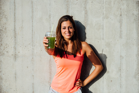 Photo for Sporty woman offering detox green smoothie. Happy sportswoman showing healthy fruit and vegetables drink. Fitness lifestyle and nutrition concept. - Royalty Free Image