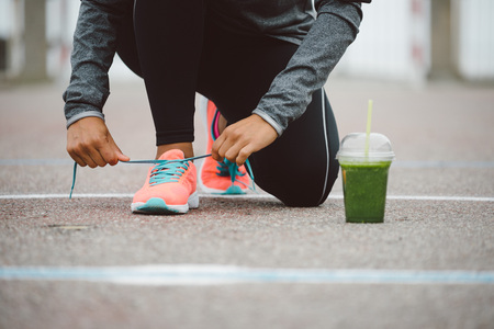 Foto de Fitness workout and healthy nutrition concept.  Detox smoothie drink and running footwear close up. Female athlete tying sport shoes laces before training outdoor. - Imagen libre de derechos