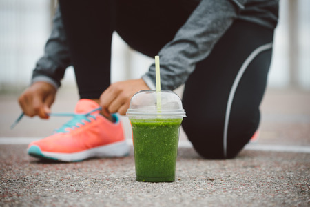 Foto de Detox smoothie drink and running footwear close up. City outdoor workout and fitness healthy nutrition concept.  Female athlete tying sport shoes laces before training. - Imagen libre de derechos