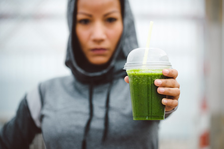 Foto per Fitness diet and nutrition concept. Tough looking urban sporty woman taking a rest for drinking nutritive detox smoothie. - Immagine Royalty Free