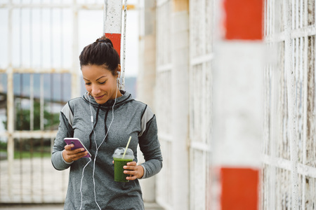 Foto per Fitness woman taking a workout rest for texting on her smartphone while drinking a nutritive detox smoothie and listening music. Healthy modern lifestyle and sport concept. - Immagine Royalty Free