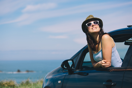 Photo pour Relaxed happy woman on summer roadtrip travel vacation leaning out car window on blue sky background. - image libre de droit