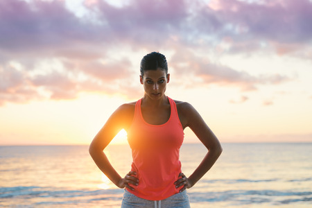 Foto de Fitness woman motivation. Challenging and motivating looking female athlete  with the sun and sea behind. - Imagen libre de derechos