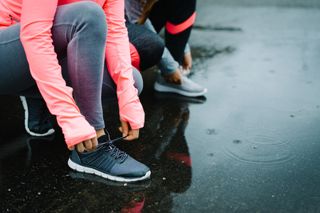Foto de Urban athletes lacing sport footwear for running over asphalt under the rain. Two women getting ready for outdoor training and fitness exercising on cold winter weather. - Imagen libre de derechos