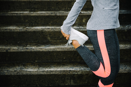 Foto de Urban workout and running concept. Woman stretching legs for warming up before exercising and climbing stairs. - Imagen libre de derechos