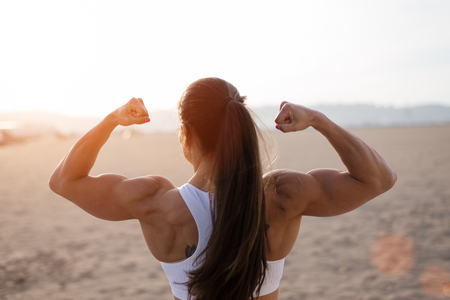 Photo for Rear view of young fit woman flexing her biceps at urban beach. - Royalty Free Image