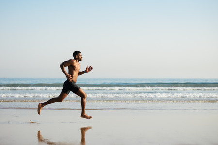 Photo for Black fit man running barefoot by the sea on the beach. Powerful runner training outdoor on summer. - Royalty Free Image