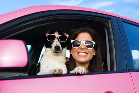 Photo pour Woman and dog in pink car on summer road trip vacation. Funny dog with sunglasses traveling. Travel with pet concept. - image libre de droit