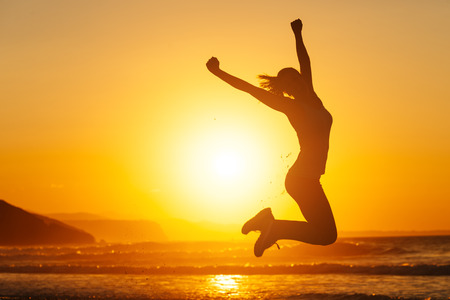 Foto de Silhouette of happy joyful woman jumping and having fun at the beach against the sunset. Freedom and leisure vacation concept. - Imagen libre de derechos