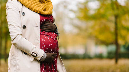 Photo pour Close up fo pregnant woman belly in autumn at the park. Gravid woman wearing raincoat, warm scarf and gloves. Pregnancy in fall season concept. - image libre de droit