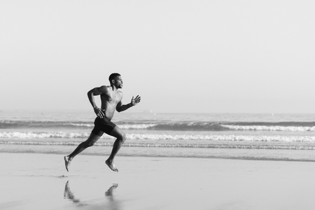 Photo for Black man running barefoot by the sea on the beach. Powerful runner sprinting and training on summer. - Royalty Free Image