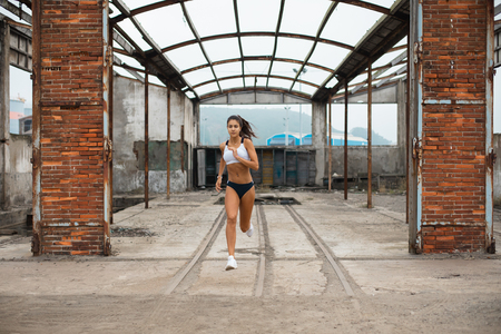 Photo for Young female athlete running at old industrial ruins. Sporty fit woman training outdoor. - Royalty Free Image