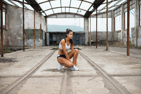Photo for Young female athlete getting ready for outdoor running workout. Sporty girl lacing footwear at old industrial ruins. - Royalty Free Image