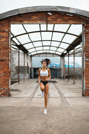 Photo for Young female athlete doing technique running in place exercise at old industrial ruins. Sporty fit woman skipping outdoor. - Royalty Free Image