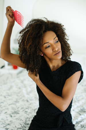 Photo pour Pretty afro hairstyle woman using comb for untangle her curly hair. Black female beauty and style tips concept. - image libre de droit