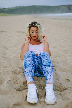Photo for Fit muscular sporty young woman doing sit ups for core training at the beach. Summer morning outdoor fitness workout. - Royalty Free Image
