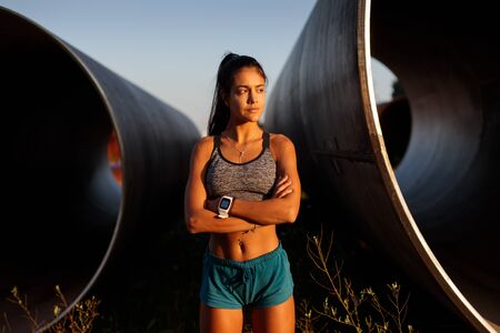 Photo for Running motivation and success. Female young athlete portrait standing with arms crossed on industrial zone. Outdoor runner training. - Royalty Free Image