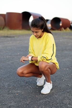 Photo for Sporty young woman timing outdoor workout. Female athlete getting ready for running. - Royalty Free Image