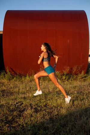 Photo for Side view of fit female athlete running on urban industrial zone. Young woman exercising outdoor. - Royalty Free Image