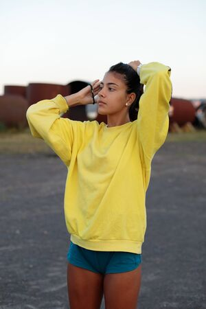 Photo for Sporty teenager getting ready for running workout. Young female athlete training outdoor on urban industrial zone. - Royalty Free Image