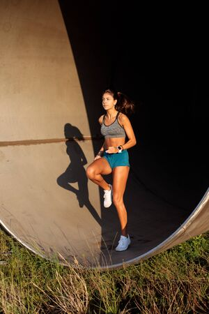 Photo for Fit female athlete doing running in place exercise on urban industrial zone. - Royalty Free Image