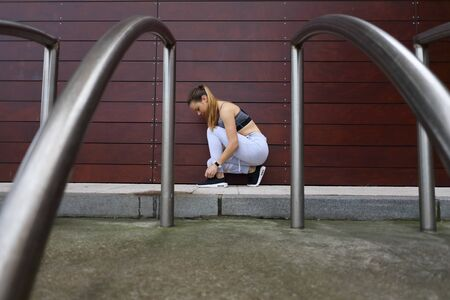 Photo for Young female athlete getting ready for outdoor urban fitness and running workout. Sporty girl lacing footwear. - Royalty Free Image