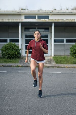 Photo for Female athlete running in place. Sporty young woman training on asphalt. - Royalty Free Image