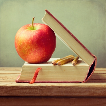 Old book and apple on wooden table over grunge background. Back to school concept