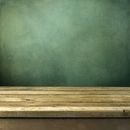 Photo pour Wooden deck table on green grunge background - image libre de droit