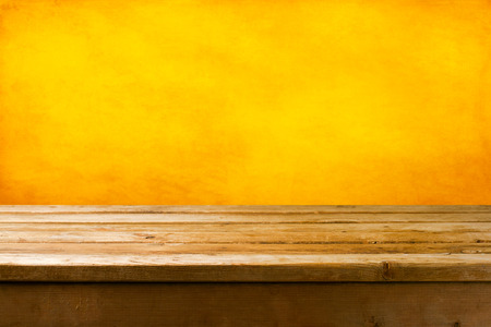 Foto de Background with wooden deck tabletop and yellow grunge wall - Imagen libre de derechos