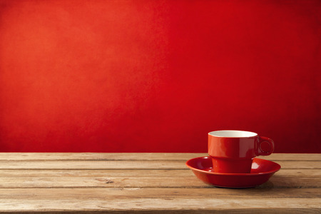 Foto per Red coffee cup on wooden table over red grunge background - Immagine Royalty Free