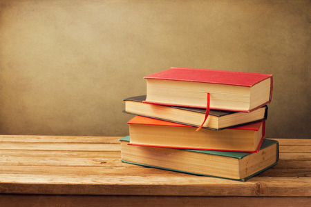 Photo for Vintage old books on wooden deck tabletop against grunge wall - Royalty Free Image