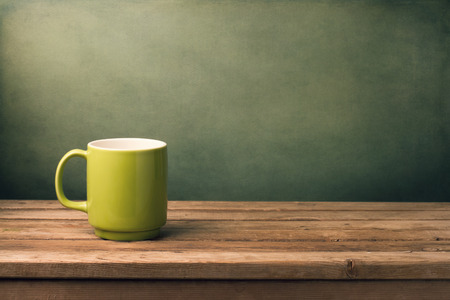 Foto für Green mug on wooden table over grunge background - Lizenzfreies Bild