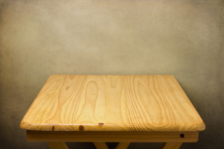 Background with wooden table over grunge wall
